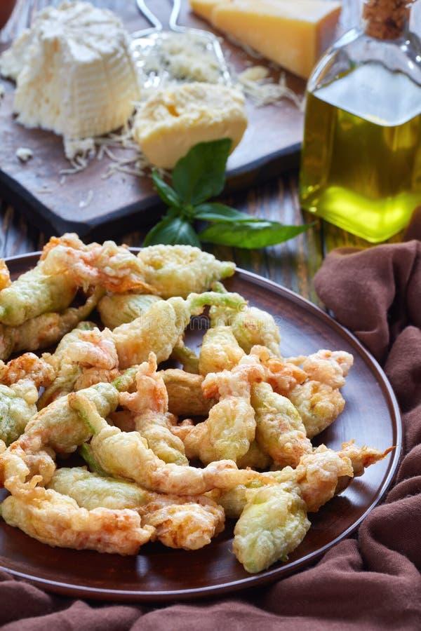 Fiori fritti nel grasso bollente dello zucchini su un piatto fotografia stock