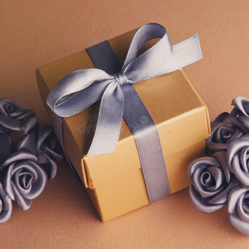 Fiori grigi e contenitore di regalo dorato fotografia stock libera da diritti
