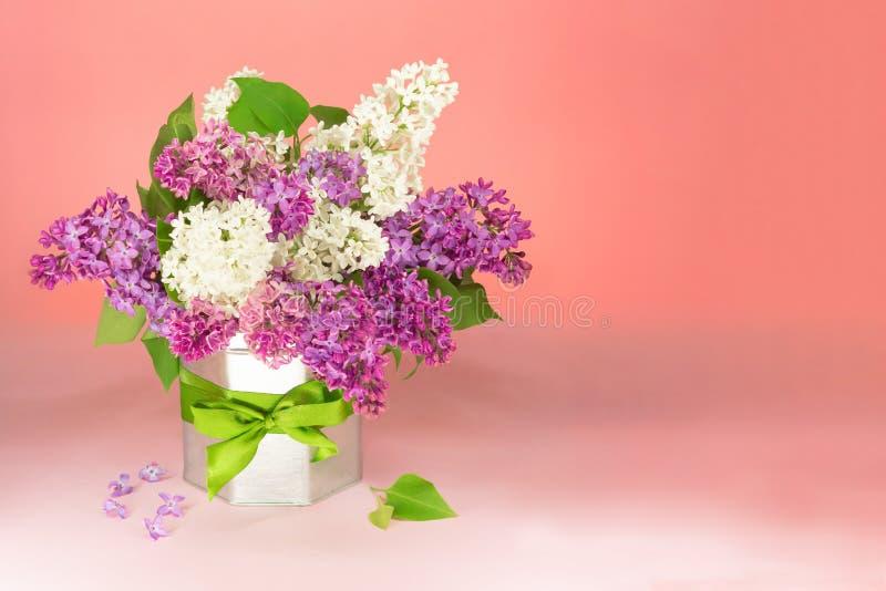 Fiori lilla bianchi e porpora del mazzo in vaso in un vaso con un arco del regalo sulla tavola, spazio della copia Fondo rosa fotografia stock