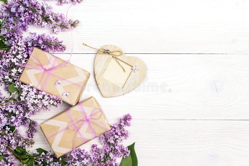 Fiori lilla con i contenitori di regalo e struttura del cuore su fondo di legno bianco immagini stock