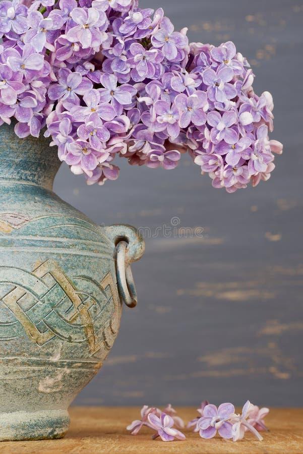 Fiori lilla freschi in un lanciatore ceramico sopra fondo blu immagini stock libere da diritti