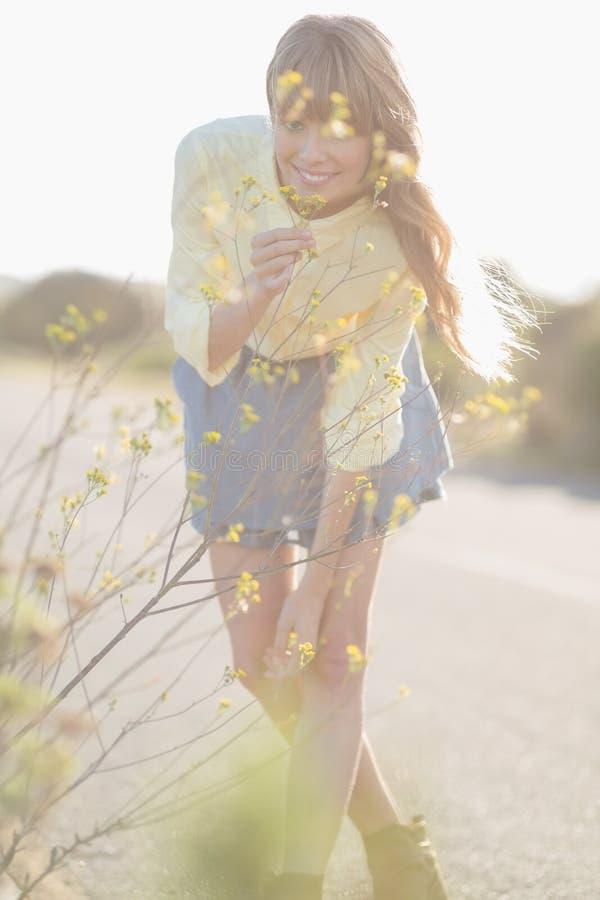 Fiori odoranti della ragazza allegra dei pantaloni a vita bassa fotografie stock