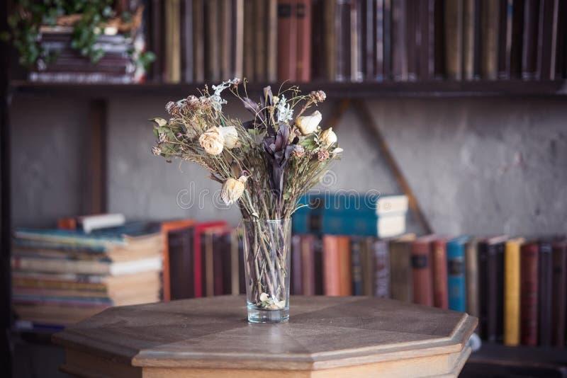 Fiori secchi in un vaso sulla tavola delle biblioteche fotografie stock libere da diritti
