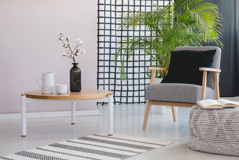 Fiori sulla tavola di legno accanto alla poltrona nell'interno del salone con la pianta ed il pouf Foto reale illustrazione di stock