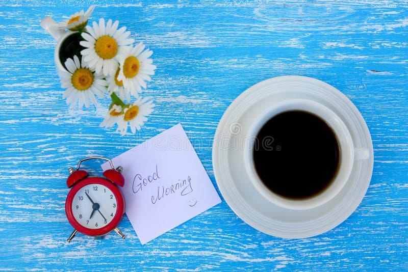 Fiori, sveglia e tazza di caffè della margherita con la nota di buongiorno immagine stock libera da diritti
