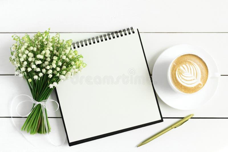Fiori, tazza di caffè e taccuino del mughetto fotografia stock
