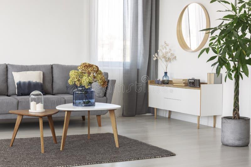 Fiori in vaso di vetro blu sul tavolino da salotto di legno in salone elegante interno con mobilia di legno bianca ed il sofà com immagini stock