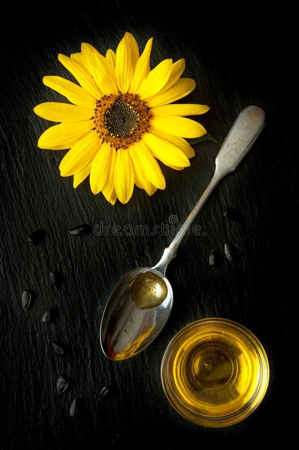 Fiorisca l'olio di cartamo e del girasole in un cucchiaio fotografia stock