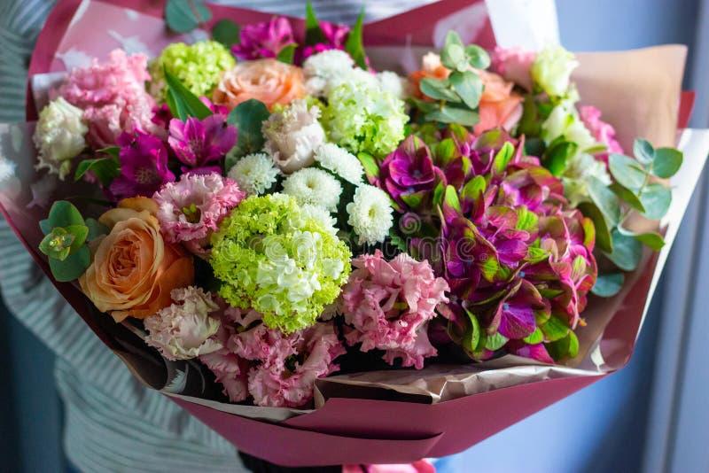 Fiorista che tiene un mazzo variopinto dei fiori nel suo fondo floreale delle mani fotografie stock libere da diritti