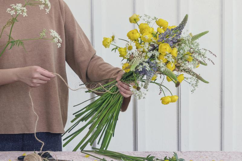 Fiorista della donna che fa il mazzo del fiore sulla tavola fotografie stock