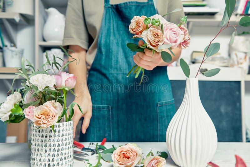 Fiorista femminile unfocused nel negozio di fiore che fa bello mazzo artificiale Un insegnante di floristry nelle classi o nei co fotografie stock