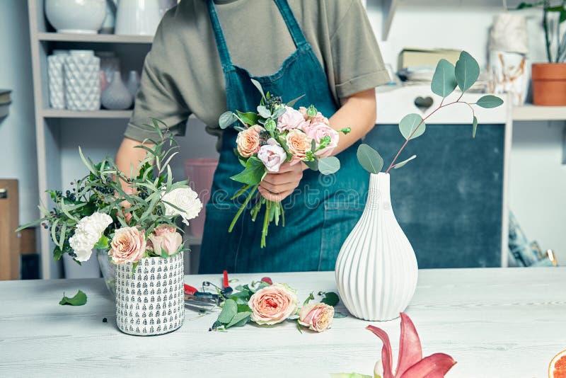 Fiorista femminile unfocused nel negozio di fiore che fa bello mazzo artificiale Un insegnante di floristry nelle classi o nei co fotografia stock