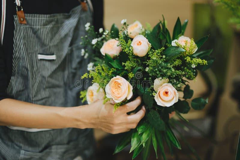 Fiorista maschio che fa bello mazzo al negozio di fiore immagini stock libere da diritti