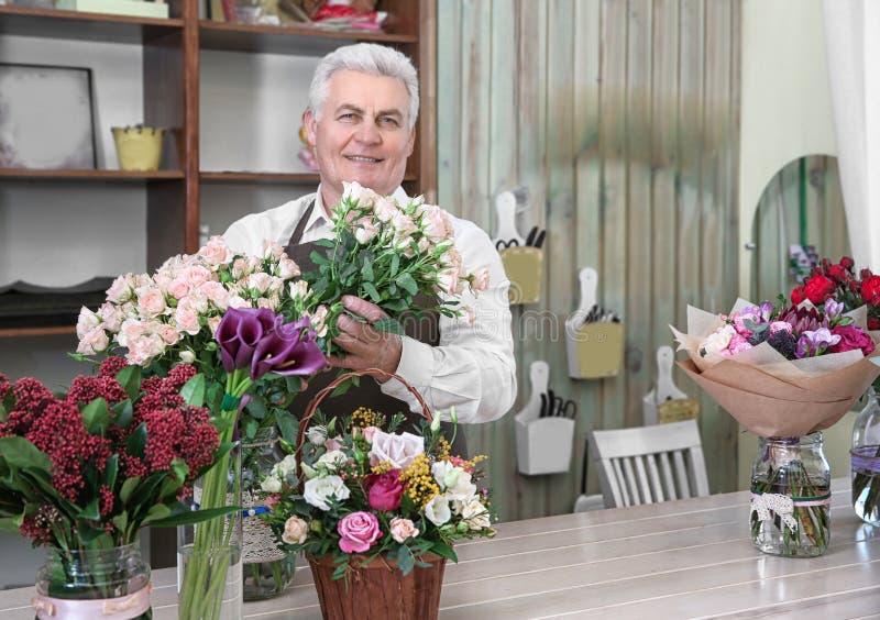 Fiorista maschio che prende cura dei fiori fotografia stock libera da diritti
