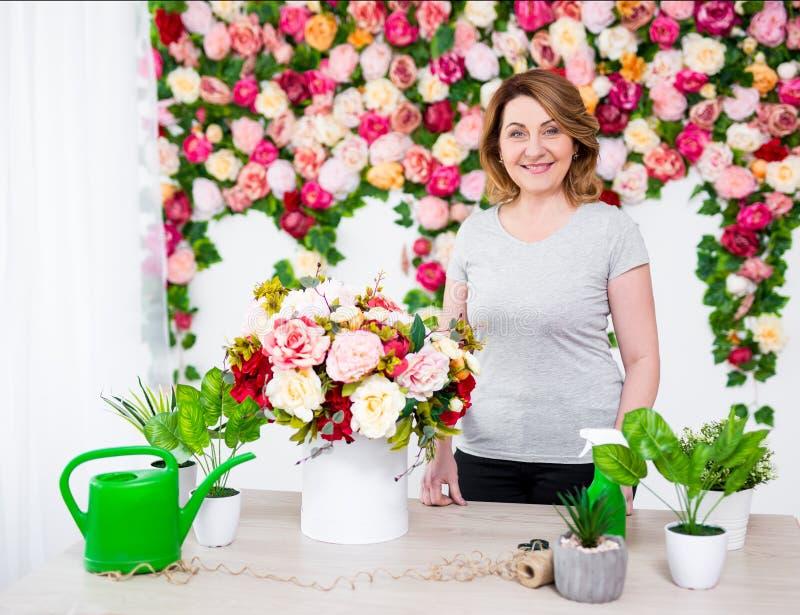 Fiorista o giardiniere femminile maturo che lavora nel negozio di fiore immagine stock