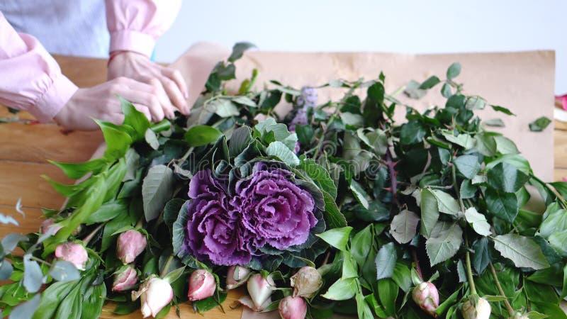Fiorista professionista che avvolge i fiori in carta al negozio di fiore fotografia stock libera da diritti