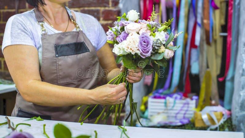 Fiorista professionista che sistema il mazzo di nozze del fiore nello studio di progettazione floreale immagini stock