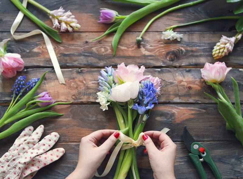 Fiorista sul lavoro Donna che fa mazzo dei fiori della molla fotografia stock