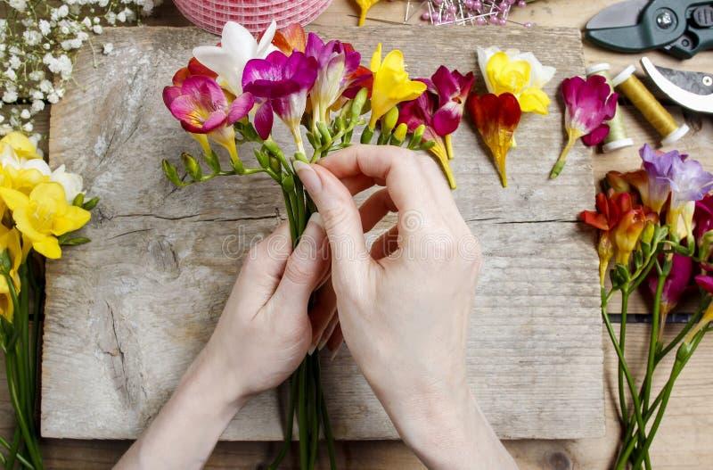 Fiorista sul lavoro Donna che fa mazzo dei fiori di fresia fotografie stock