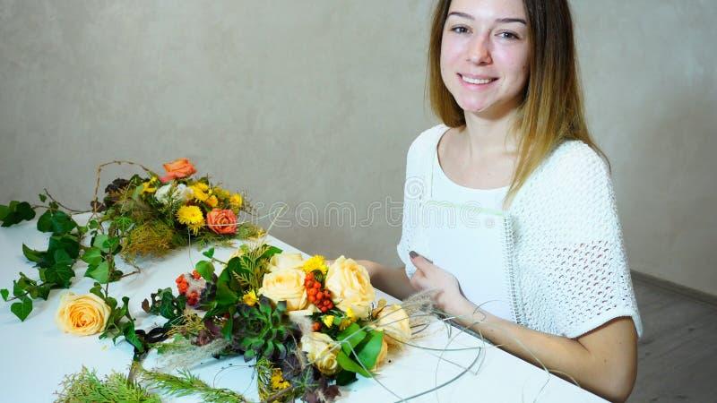 Fiorista sveglio della tenuta della giovane donna con il sorriso e la posa con più gest immagine stock libera da diritti