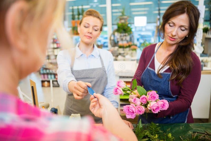 Fioristi che vendono il negozio di Rose Bouquet To Customer In immagine stock libera da diritti