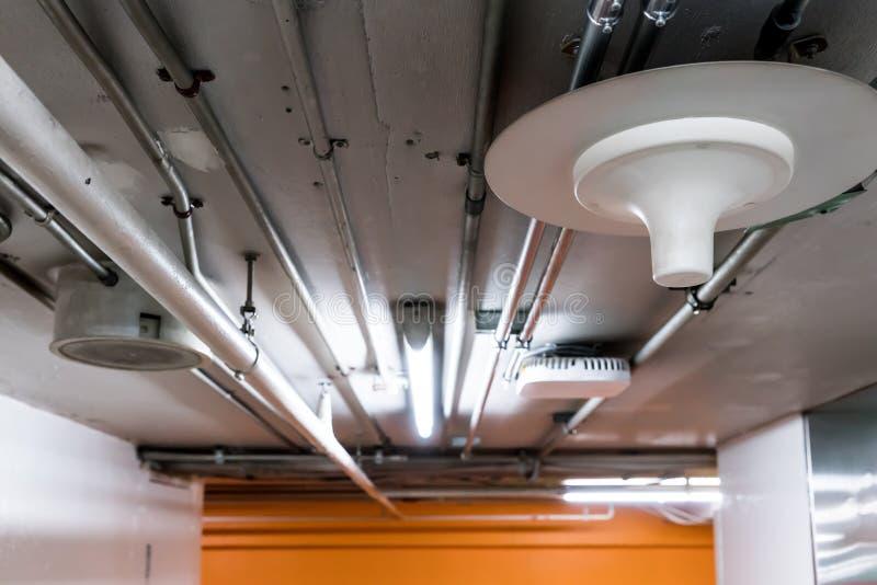 Fios bondes nas tubulações de alumínio que correm através do cei concreto fotografia de stock
