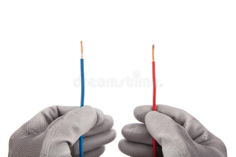 Fios vermelhos e azuis nas mãos com luvas fotografia de stock royalty free
