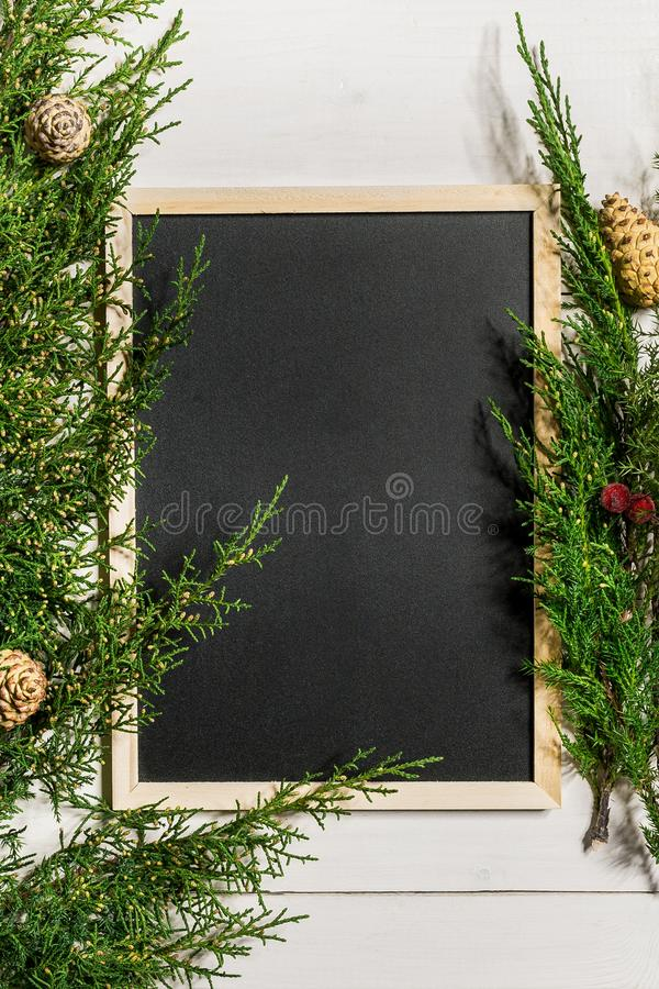 Fir branches border and black chalk board on white wooden background, good for christmas backdrop royalty free stock photo