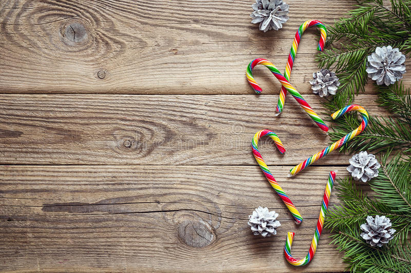 Fir branches with cones and Christmas Candy Canes on old wooden royalty free stock images