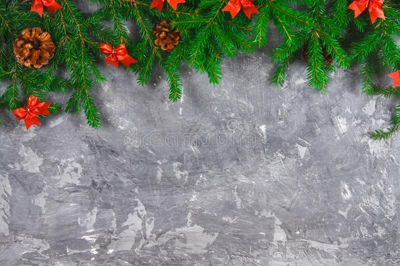 Fir branches with cones and red bows on top of a gray concrete background. New Year Christmas. Free space for text. Fir branches with cones and red bows on top royalty free stock photo
