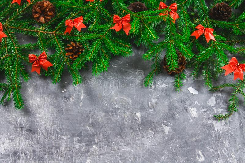 Fir branches with cones and red bows on top of a gray concrete background. New Year Christmas. Free space for text. Fir branches with cones and red bows on top royalty free stock images