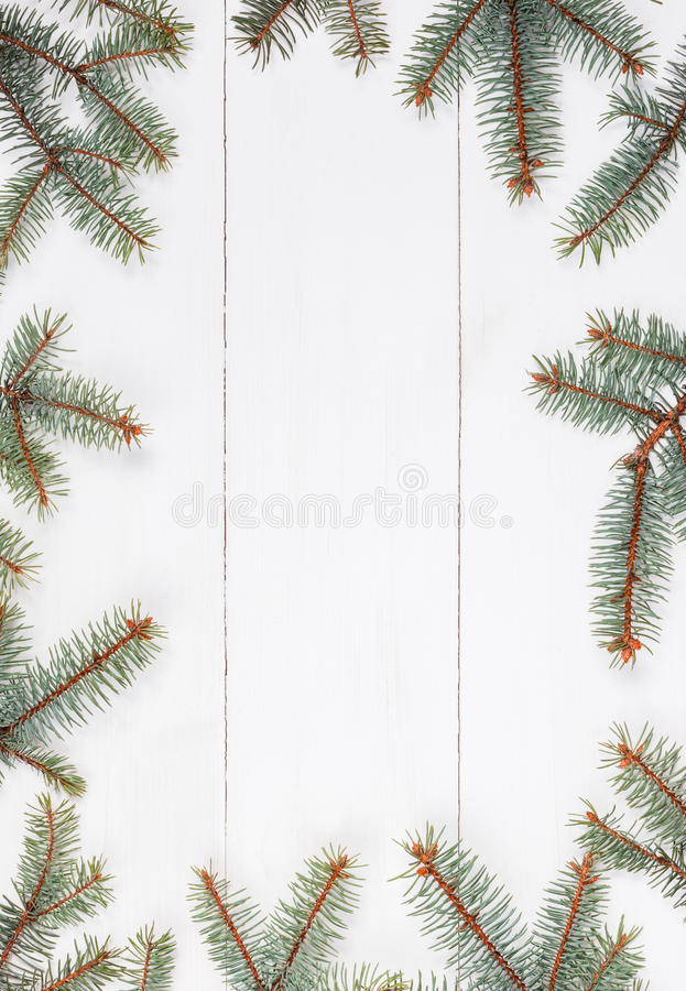 Fir branches in form of frame on white wooden table. Christmas and Happy New Year composition.Flat lay, top. View stock photos