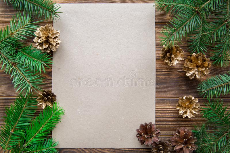 Fir branches and golden cones on brown wooden table background. Free card for Christmas greeting. Space for text stock photo