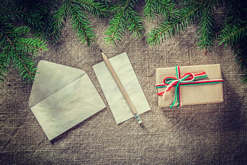 Fir tree branch handmade present box paper pencil on burlap back royalty free stock images