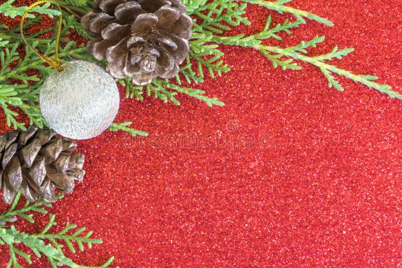 Fir tree branch with pine cones and silver ornament, on red glitter surface stock images