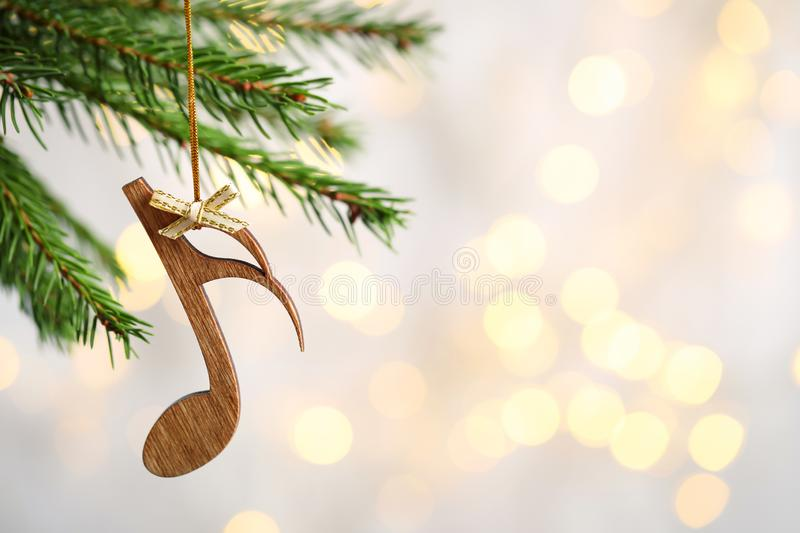 Fir tree branch with wooden note against blurred lights. Christmas music. Fir tree branch with wooden note against blurred lights, space for text. Christmas stock photos