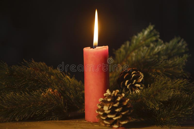 Fir tree branches with burning candle on table. Pine cones and fir tree branches with burning candle on the table. Shot with dark background stock photos