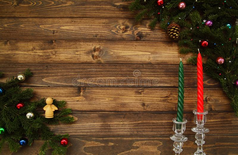 Fir tree branches with Christmas decoration and candles in chrystal candlesticks against old vintage style wooden planks. Christmas/New Year vintage concept stock image