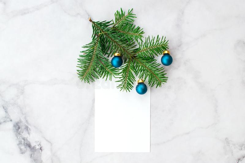 Fir-tree branches decorated with blue balls on gray marble background. New Year, Christmas and winter concept. Flat lay, top view. Free copy space royalty free stock photos