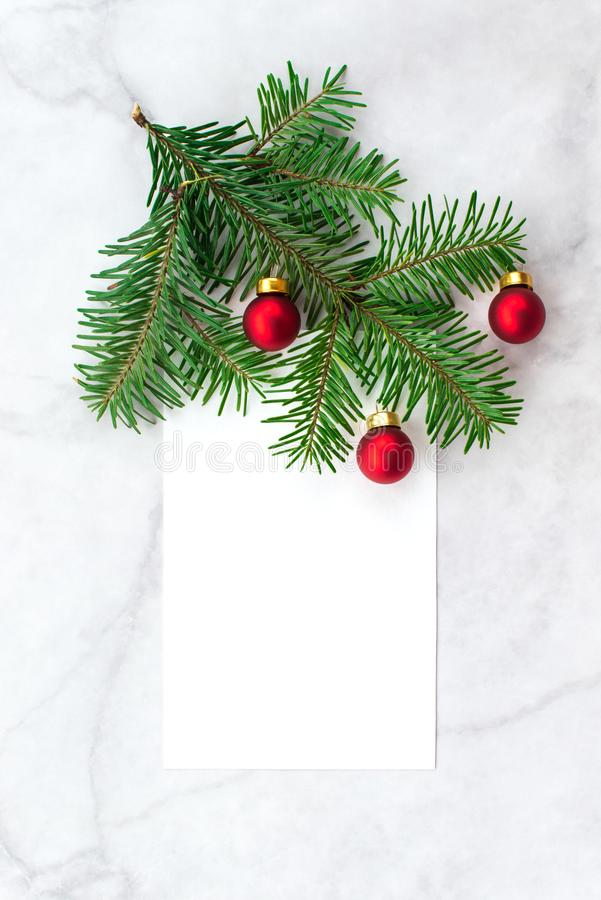 Fir-tree branches decorated with red balls on gray marble background. New Year, Christmas and winter concept. Flat lay, top view, free copy space stock image