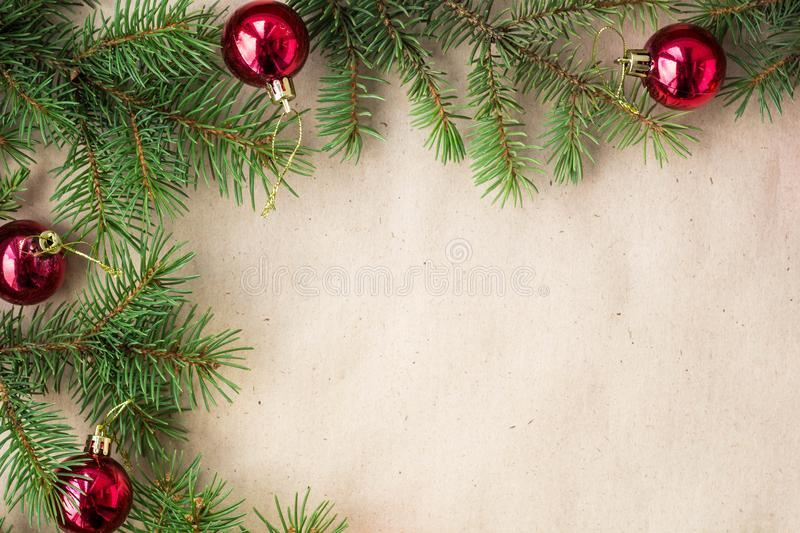 Fir tree branches decorated with red christmas balls as border on a rustic holiday background frame with copy space.  royalty free stock photos