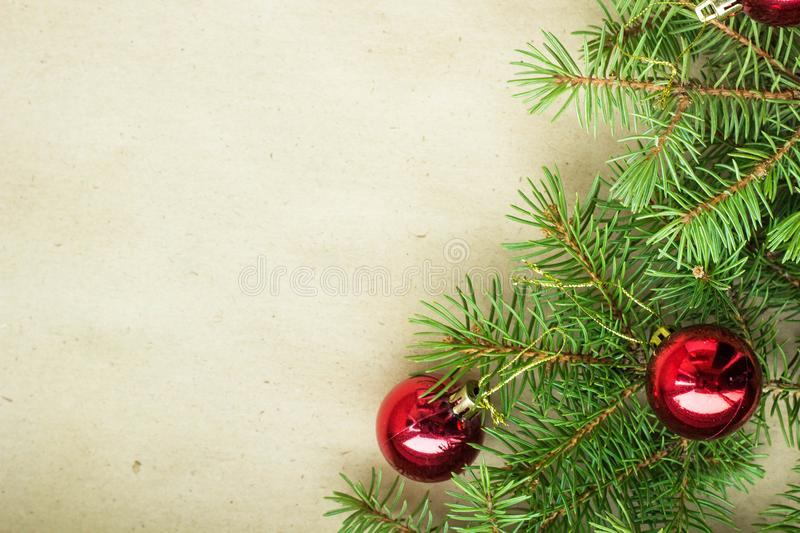 Fir tree branches decorated with red christmas balls as border on a rustic holiday background frame with copy space.  royalty free stock images