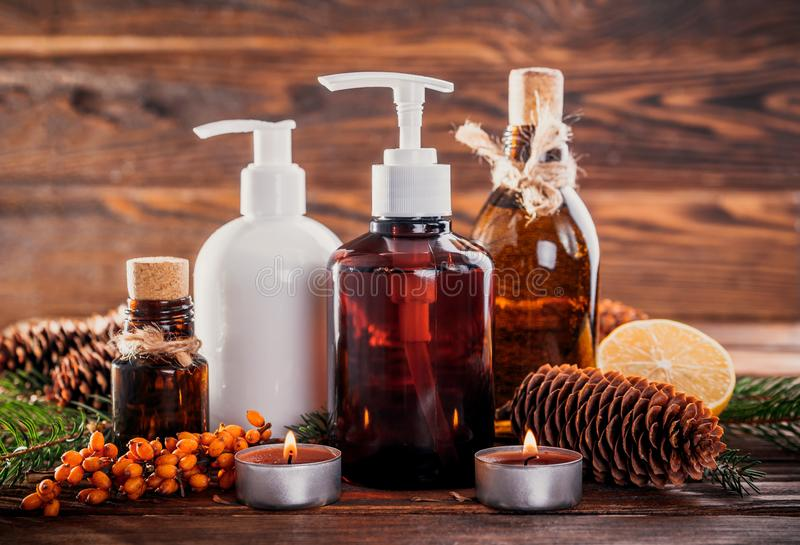 Fir tree and cones organic oils with lemon and sea buckthorn extracts. Organic cosmetics concept. Fir tree and cones organic oils with lemon and sea buckthorn stock photos