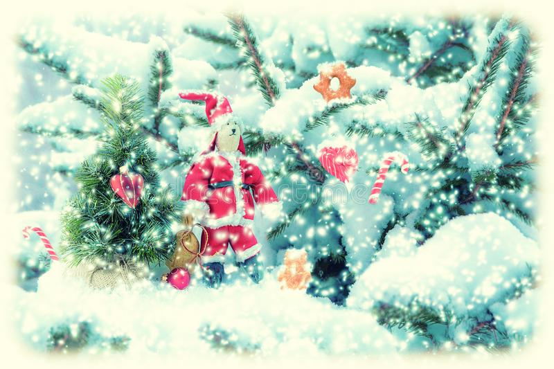 Fir tree covered snow, bunny Santa doll, candy cane, cookies, closeup. Winter Christmas greeting card manipulation background stock photography