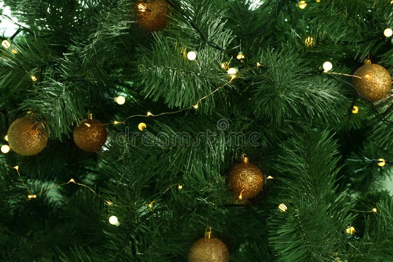 Fir tree with festive decor and glowing Christmas lights. As background stock photography
