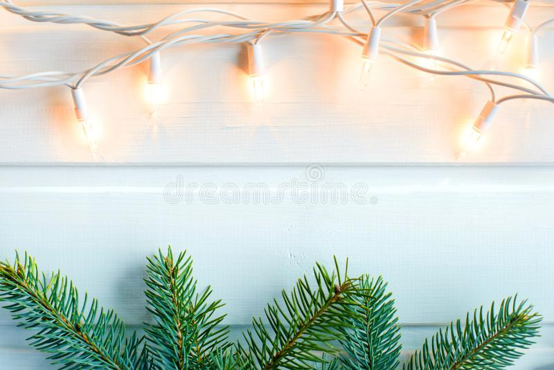 Fir-tree and warm yellow Christmas lights on white wooden background. New year concept. Free copy space. Fir-tree and warm yellow Christmas lights on white royalty free stock images