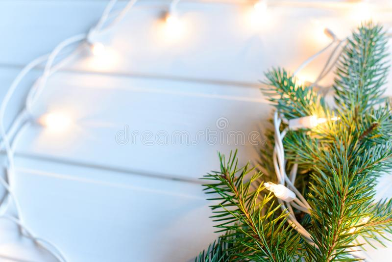 Fir-tree and warm yellow Christmas lights on white wooden background. New year concept. Free copy space. Fir-tree and warm yellow Christmas lights on white royalty free stock image