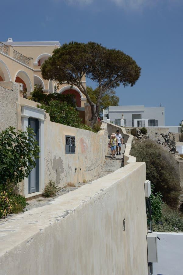 Fira街道视图与典型的希腊大厦和地中海植物和两个游人走的 库存照片