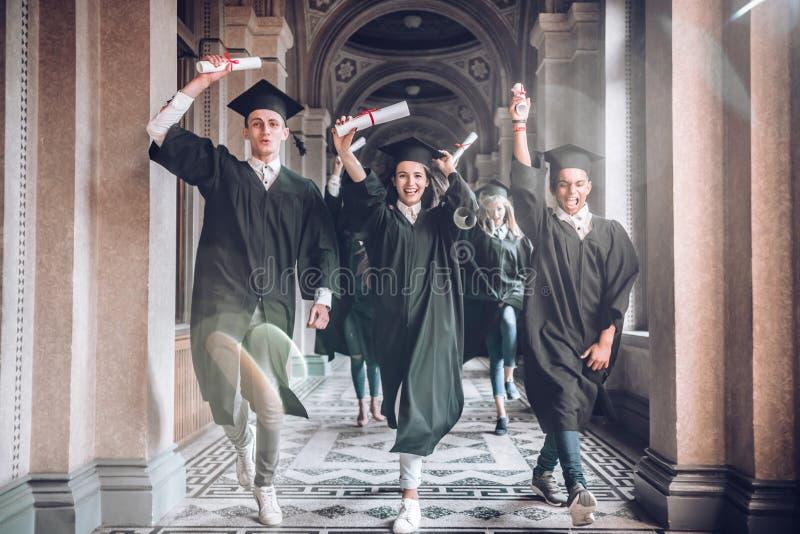 Fira deras prestationer tillsammans Universitetet var de bästa åren av deras liv! Grupp av att le att rymma för universitetsstude royaltyfri fotografi