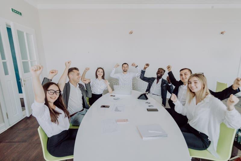 fira framgång Grupp av ungt affärsfolk som lyfter deras armar och ser lyckligt, medan sitta runt om skrivbordet tillsammans arkivfoton